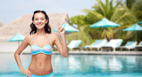 Happy woman in bikini swimsuit pointing finger up Royalty Free Stock Photos