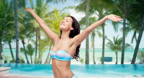 Happy woman in bikini swimsuit with raised hands. People, travel, tourism and summer concept - happy young woman in bikini swimsuit with raised hands looking up Stock Photos