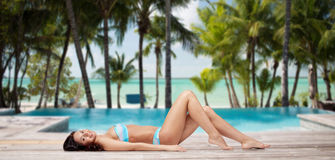 Happy woman in bikini tanning over summer beach. People, fashion, swimwear, summer and travel concept - happy young woman lying and tanning in bikini swimsuit Royalty Free Stock Images