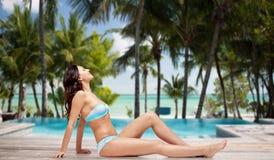 Happy woman in bikini tanning over summer beach Stock Photography