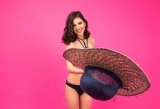 Happy woman in bikini throwing hat at camera Royalty Free Stock Image