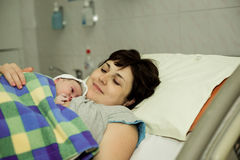 Happy woman after birth with a newborn baby Royalty Free Stock Photography