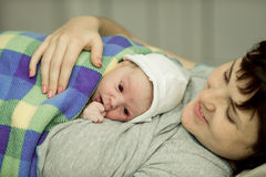 Happy woman after birth with a newborn baby Stock Photo