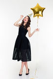 Happy woman with birthday hat prop and star shaped balloon Stock Images
