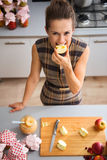 Happy woman biting into apple quarter in kitchen. Seen from above, a happy woman smiles as she is biting into a freshly-cut apple. On the kitchen counter, a Stock Image