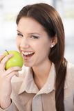 Happy woman biting an apple smiling Royalty Free Stock Images