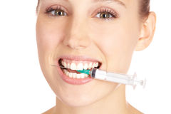 Happy woman biting on syringe Stock Photos