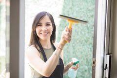 Portrait of attractive young woman cleaning windows. Happy woman in black apron cleaning window with wiper and spray at home from outside Stock Photo