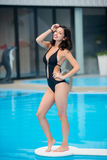 Happy woman in black bikini with shapely body posing near the swimming pool on resort vacation with blurred background Stock Photos