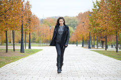 Happy woman in black coat walking autumn street Stock Photos
