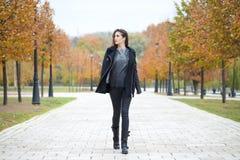 Happy woman in black coat walking autumn street Stock Photography