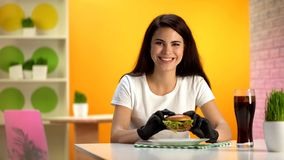 Happy woman in black rubber gloves holding hamburger and smiling at camera royalty free stock photos