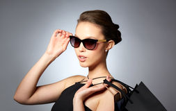 Happy woman in black sunglasses with shopping bags. Sale, fashion, people and luxury concept - happy beautiful young woman in black sunglasses with shopping bags Royalty Free Stock Photos