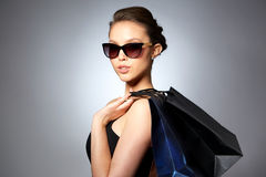 Happy woman in black sunglasses with shopping bags Stock Images