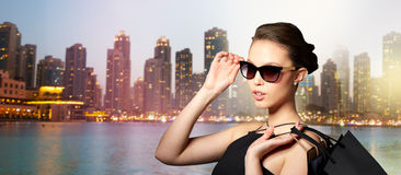 Happy woman in black sunglasses with shopping bags. Sale, tour, fashion, people and luxury concept - happy beautiful young woman in black sunglasses with Royalty Free Stock Images