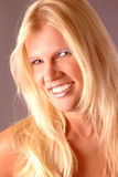 Happy woman with blond hair. Portrait of happy young woman with long blond hair and bare, shoulders; studio background Royalty Free Stock Photos