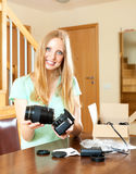 Happy woman  with blond hair unpacking new digital camera at hom. Happy woman unpacking new digital camera at home in living room Royalty Free Stock Image