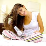 Happy woman blow drying long hair at home. Cute young woman blow dry long wavy hair sitting on bed Royalty Free Stock Image