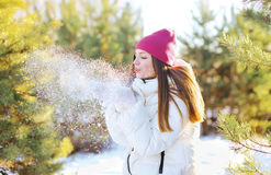 Happy woman blowing on the snow outdoors in sunny winter day Stock Photo