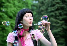 Happy woman blowing soap bubbles Royalty Free Stock Image