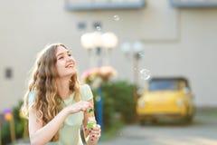 Happy woman blowing soap bubbles Stock Photo
