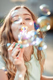 Happy woman blowing soap bubbles Royalty Free Stock Images