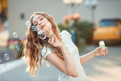 Happy woman blowing soap bubbles Royalty Free Stock Photography