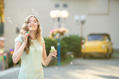 Happy woman blowing soap bubbles. focus on soap bubbles Stock Images