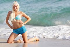 Happy woman in blue bikini on sea background Stock Photos
