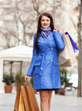 Happy woman in blue cloak with shopping bags Stock Photography