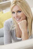 Happy Woman With Blue Eyes Laying on Sofa Royalty Free Stock Image