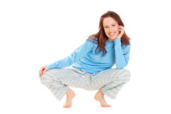 Happy woman in blue pyjamas. Sitting on the floor Stock Photography