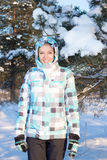 Happy woman in blue sporty checkered jacket walking in winter fo Stock Image