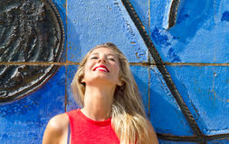 Happy woman on a blue wall Stock Photo