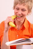 Happy woman with book is biting banana. Fresh stock photo