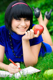 Happy woman with book outdoors. Happy young woman writing in book in countryside with ripe apple, green nature background Stock Image