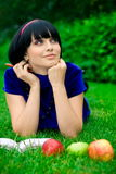 Happy woman with book outdoors. Happy young woman writing in book in countryside with ripe apple, green nature background Royalty Free Stock Photo