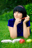 Happy woman with book outdoors. Happy young woman writing in book in countryside with ripe apple, green nature background Stock Photography