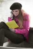Happy woman with book outdoors Stock Photo