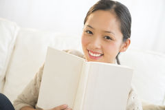 Happy Woman With Book Sitting On Sofa Stock Photo