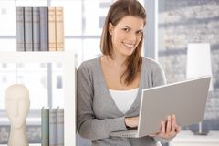 Happy woman at bookcase with computer. Happy woman standing at bookcase with laptop computer handheld, smiling at camera