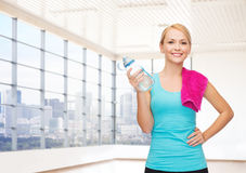 Happy woman with bottle of water and towel in gym Stock Photography