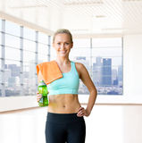Happy woman with bottle of water and towel in gym Stock Image
