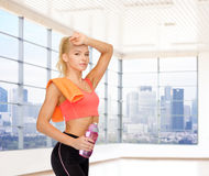 Happy woman with bottle of water and towel in gym Royalty Free Stock Images