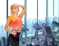 Happy woman with bottle of water and towel in gym Stock Photo