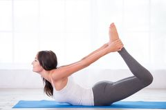 Happy woman in bow pose Stock Photo
