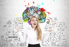 Happy woman, brain and cogs. Portrait of a happy woman screaming with joy while standing near a concrete wall with a colorful brain sketch and cogs Stock Photos