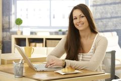 Happy woman with breakfast and laptop Stock Photo