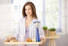 Happy woman with breakfast tray. Happy woman standing with breakfast tray in living room, smiling at camera Stock Photos