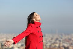 Happy woman breathing in the city. Side view portrait of a happy woman breathing deep in the city royalty free stock image